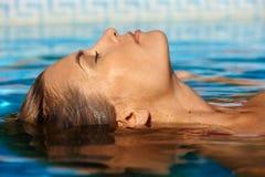 Молодая женщина в плавательном бассеине стоковые изображения rf