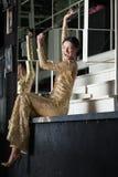 Молодая женщина в платье золота имеет потеху на таблице адвокатского сословия Стоковые Фото