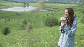 Молодая женщина в плаще идет на поле с цветками видеоматериал