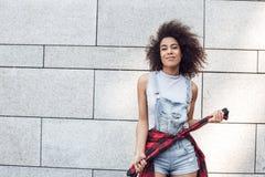 Молодая женщина в положении улицы города изолированная на серый представлять рукавов куртки удерживания стены уверенный стоковые изображения