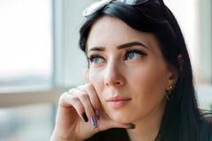 Молодая женщина в превидении смотрит вне огромное окно к улице стоковые изображения