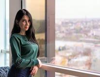 Молодая женщина в превидении смотрит вне огромное окно к улице стоковые фотографии rf