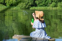Молодая женщина в пузырях платья и соломенной шляпы дуя против t стоковые изображения