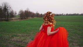 Молодая женщина в роскошном красном платье бежит вдоль зеленых поля и улыбок акции видеоматериалы