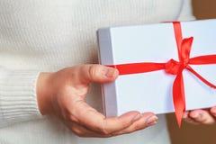 Молодая женщина в связанном белом свитере держа в подарочной коробке белизны рук стоковые изображения rf