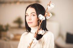 Молодая женщина в связанном белом свитере платья с ветвью конца-вверх хлопка Девушка в винтажном романтичном интерьере стоковые фотографии rf