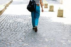 Молодая женщина в случайных одеждах и рюкзаке идет вниз по улице Женщина смотрит от задней части o стоковые фотографии rf