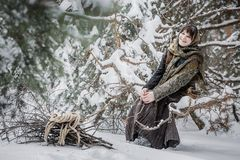 Молодая женщина в старых одеждах сидя с зарослью в характере леса зимы от сказки Стоковые Фотографии RF