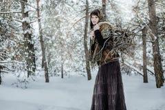 Молодая женщина в старых одеждах стоит с зарослью в характере леса зимы от сказки Стоковое Изображение