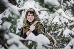 Молодая женщина в старых одеждах стоит с зарослью в характере леса зимы от сказки Стоковые Изображения