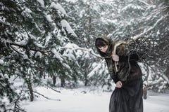 Молодая женщина в старых одеждах стоит с зарослью в характере леса зимы от сказки Стоковое Фото