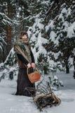 Молодая женщина в старых одеждах стоит с корзиной и зарослью в снеге в лесе зимы Стоковые Фотографии RF