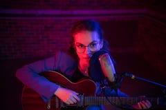Молодая женщина в стеклах играя гитару и поя mic в неоновом освещении стоковые изображения
