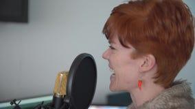 Молодая женщина в студии для того чтобы записать бирку голоса для коммерчески проектов на микрофоне студии акции видеоматериалы