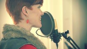 Молодая женщина в студии для того чтобы записать бирку голоса для коммерчески проектов на микрофоне студии видеоматериал