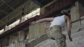 Молодая женщина в тренировке военной формы в получившемся отказ здании Девушка взбираясь вверх бетонные плиты r акции видеоматериалы