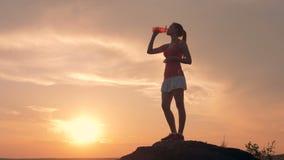 Молодая женщина в форме спорт стоит на утесе и выпивать сток-видео