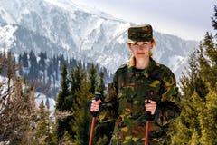 Молодая женщина в хаки форме с идя ручками на предпосылке снег-покрытых гор Стоковые Фото