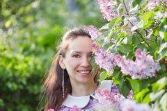 Молодая женщина в цветках сирени Стоковое Фото