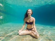 Молодая женщина в черном бикини в положении йоги подводном в аквариуме подныривания, полной съемке тела, вид спереди стоковые изображения rf