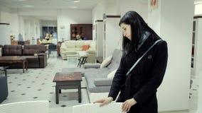 Молодая женщина в черном пальто в мебельном магазине выбирает мебель сток-видео