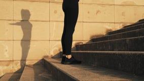 Молодая женщина в черном tracksuit бежать вверх шаги Девушка на беге Погода солнечна и тепла Маленькая девочка бежит