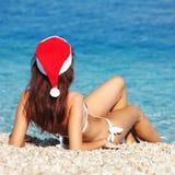 Молодая женщина в шлеме santa сидя на пляже Стоковое фото RF