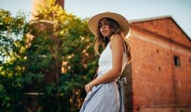 Молодая женщина в шляпе идет на улицу города рядом с зданием и деревом стоковые фотографии rf