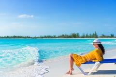 Молодая женщина в шляпе на тропическом пляже ослабляя на sunbed Стоковое Изображение