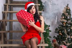 Молодая женщина в шляпе santa и в красном платье трясет коробку с Стоковая Фотография RF