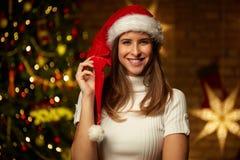 Молодая женщина в шляпе santa с светами рождества стоковая фотография