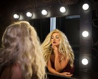 Молодая женщина в элегантном платье смотрит себя в зеркале стоковое изображение rf