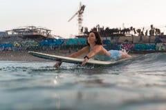 Молодая женщина в ярком бикини занимаясь серфингом на доске в океане Стоковое Фото