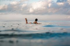 Молодая женщина в ярком бикини занимаясь серфингом на доске в океане Стоковые Фото