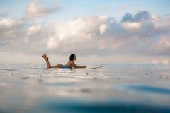 Молодая женщина в ярком бикини занимаясь серфингом на доске в океане Стоковая Фотография RF