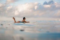Молодая женщина в ярком бикини занимаясь серфингом на доске в океане Стоковые Фотографии RF