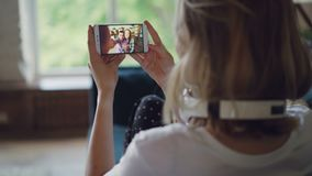 Молодая женщина говорит к друзьям онлайн при smartphone смотря экран и говоря сидеть на кресле в современном сток-видео