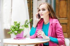 Молодая женщина говорит на телефоне в кафе Образ жизни концепции Стоковая Фотография RF