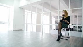 Молодая женщина говорит на телефоне пока сидящ в современном офисе видеоматериал