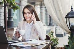 Молодая женщина говоря на телефоне и выпивая кофе Стоковые Изображения