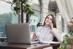 Молодая женщина говоря на телефоне и выпивая кофе Стоковая Фотография RF