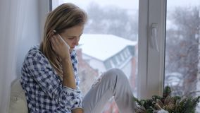 Молодая женщина говоря на телефоне окном на windowsill видеоматериал