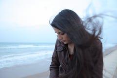 Молодая женщина говоря на телефоне рядом с морем в зиме Стоковые Изображения