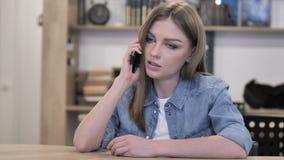 Молодая женщина говоря по телефону, обсуждению