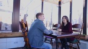 Молодая женщина говоря с супругом на таблице кафа акции видеоматериалы