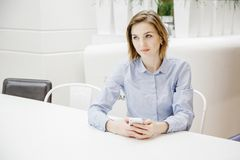 Молодая женщина говоря через телефон Девушка сидит на таблице и делает заказ женщина дела 2 Стоковые Изображения RF