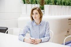 Молодая женщина говоря через телефон Девушка сидит на таблице и делает заказ женщина дела 2 Стоковая Фотография