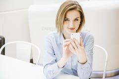 Молодая женщина говоря через телефон Девушка сидит на таблице и делает заказ женщина дела 2 Стоковое Изображение