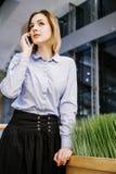 Молодая женщина говоря через телефон Девушка сидит на таблице и делает заказ женщина дела 2 Стоковое фото RF