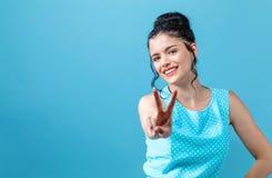 Молодая женщина давая знак мира стоковая фотография rf
